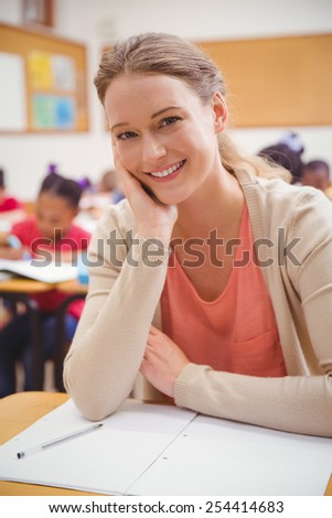 Pretty teacher smiling at camera with head in hand at the elementary school - stock photo