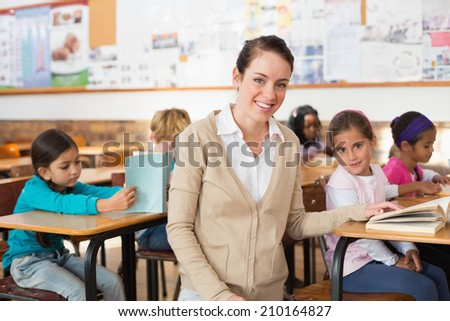 Pretty teacher smiling at camera with her class at the elementary school - stock photo