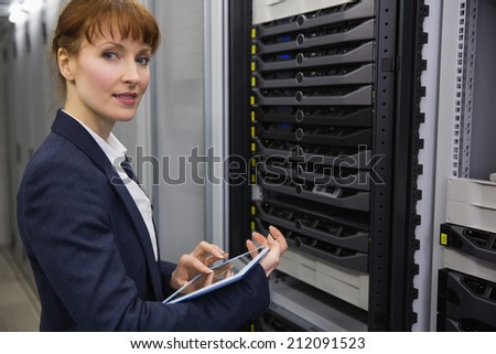 Pretty technician using tablet pc while working on servers in large data center - stock photo