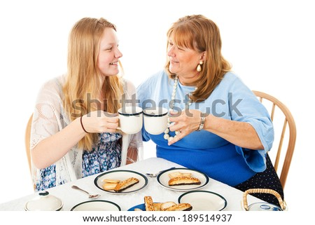 Pretty teen celebrates Mother's Day with a tea party for her mom.  Isolated on white.   - stock photo