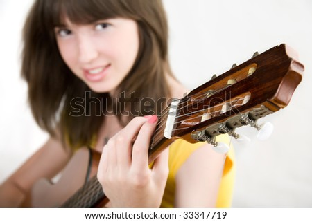Pretty teen girl playing guitar - stock photo