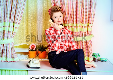 Pretty teen girl talking on the phone on a pink kitchen. Beauty, youth fashion. Pin-up style. - stock photo