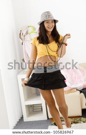 Pretty teenage girl posing in mini skirt, laughing. - stock photo
