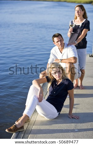 Pretty teenage girl relaxing on dock by water, parents behind - stock photo