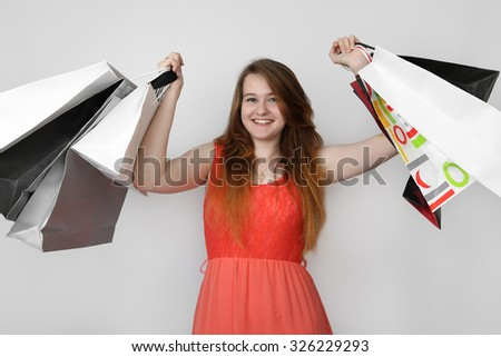 Pretty teenage girl with happy face and shopping bags in raised hands on gray background - stock photo