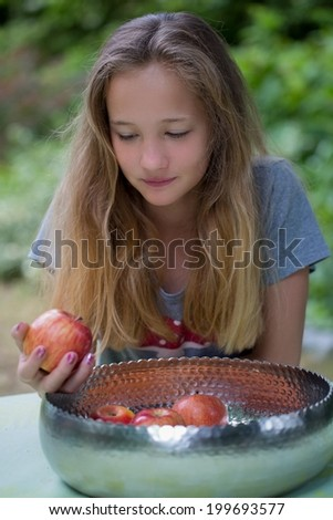 Pretty teenage girl with long blond hair choosing a fresh red apple form a bowl of freshly harvested fruit on a garden table for a tasty healthy summer snack - stock photo