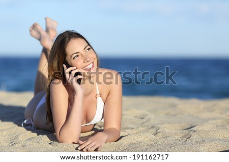 Pretty teenager girl on the phone lying on the beach with the horizon in the background - stock photo