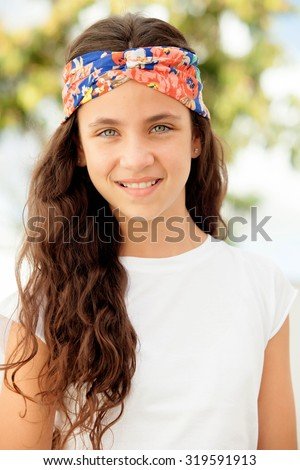 Pretty teenager girl with a flowered headband outdoor - stock photo