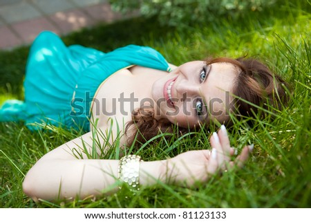 pretty teenager lying down on green grass in blue dress - stock photo