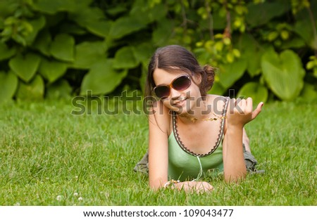 Pretty teenager on grass with sunglasses in the park - stock photo
