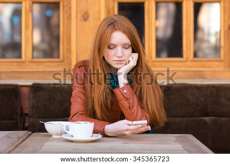 Pretty thoughtful girl with beautiful long red hair in leather jacket using smartphone and drinking coffee in outdoor cafe - stock photo