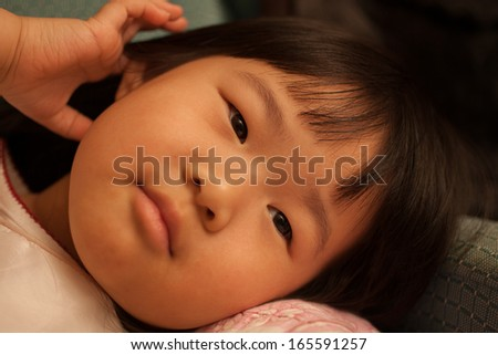 Pretty toddler asian girl laying down and watching tv - stock photo