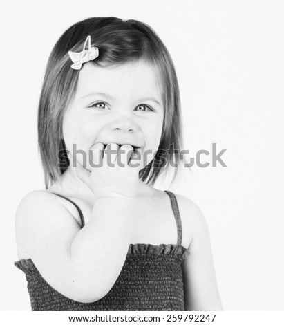 Pretty toddler girl with fingers in her mouth - stock photo