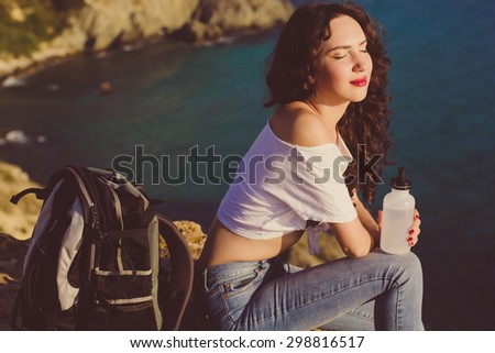 Pretty traveler girl backpacker is drinking water on rock peak over sea view with backpack, summer vacations - stock photo