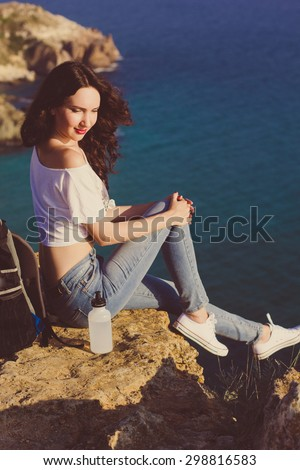 Pretty traveler girl backpacker is sitting on rock peak over sea view with backpack, summer time - stock photo