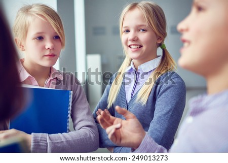 Pretty twins during chat with schoolmates - stock photo