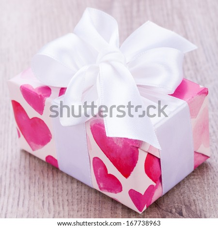 Pretty Valentines gift with hearts on the giftwrap on a big white ornamental bow on top, closeup high angle view of a gift for a loved one or sweetheart - stock photo