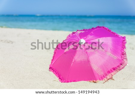 Pretty vibrant pink beach umbrella on the beautiful golden sand of an idyllic tropical beach conceptual of a summer vacation or getaway - stock photo