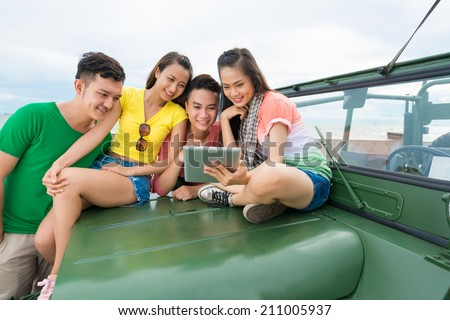Pretty Vietnamese girl sitting on the car hood and showing her friends something on the digital tablet - stock photo