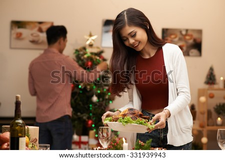 Pretty Vietnamese woman laying the table while her husband decorating Christmas tree - stock photo
