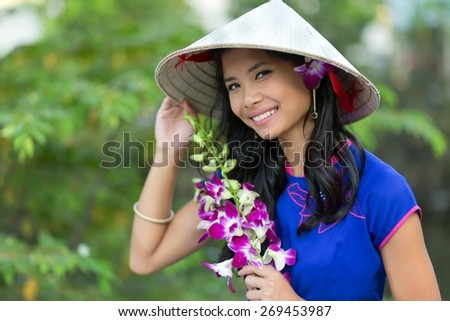 Pretty Vietnamese woman wearing a traditional conical hat holding orchid flower bunch - stock photo