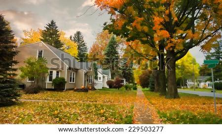 pretty village street in autumn - stock photo