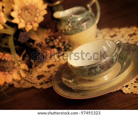 Pretty vintage china cup with saucer, plate and creamer - stock photo