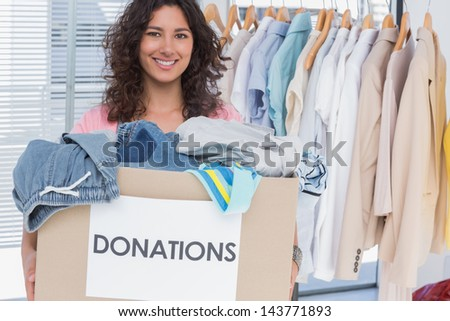 Pretty volunteer holding clothes donation box - stock photo