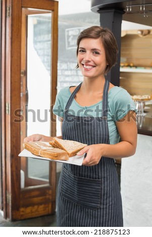 Pretty waitress holding plate of food at the coffee shop - stock photo