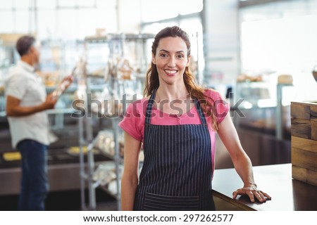 Pretty waitress leaning on counter at the bakery - stock photo