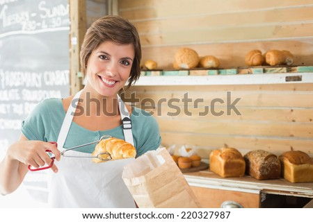 Pretty waitress picking up croissant at the coffee shop - stock photo