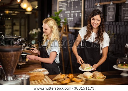 Pretty waitresses behind the counter working at the coffee shop - stock photo