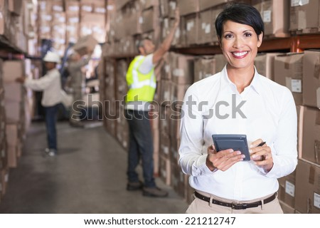 Pretty warehouse manager using calculator in a large warehouse - stock photo