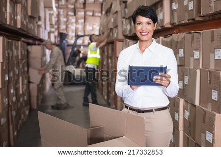 Pretty warehouse manager using tablet pc in a large warehouse - stock photo