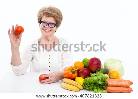 Pretty woman a pensioner showing tomato in hand while sitting near fresh fruit and vegetables, white background - stock photo