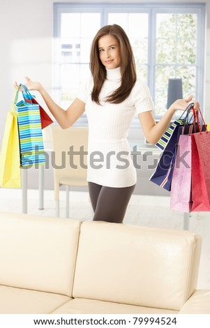 Pretty woman after shopping standing at home, posing holding colorful shopping bags happily.? - stock photo