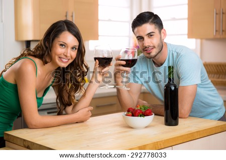Pretty woman and handsome man portrait with some red wine at home indoors smiling - stock photo