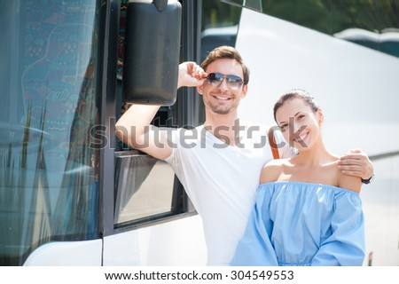 Pretty woman and man are standing near a bus. They are traveling with joy. The guy is embracing his girlfriend with love and adjusting his eyeglasses. They are smiling - stock photo