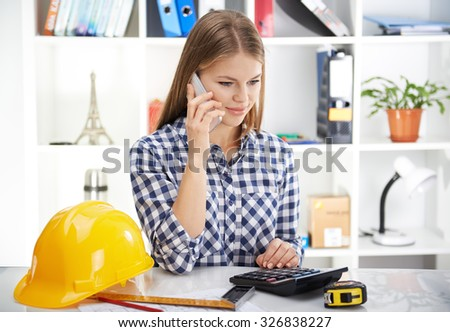Pretty woman architect making estimate of new construction project. Young businesswoman with phone and draft in the office.  - stock photo
