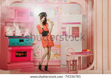 Pretty woman as a doll in the kitchen - stock photo