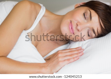 Pretty woman asleep in bed - stock photo