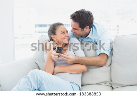 Pretty woman being surprised by a marraige proposal at home in the living room - stock photo