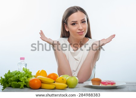 Pretty woman can not make a decision what she should eat. She is looking at the camera hopefully. The woman is sitting at the table on which fruits and donuts are situated. Isolated on a white - stock photo