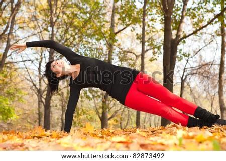 Pretty woman doing yoga exercises in the autumn park - stock photo