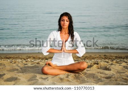 Pretty woman doing yoga on the beach - stock photo