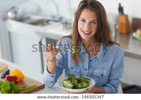 Pretty woman eating a salad in the kitchen - stock photo