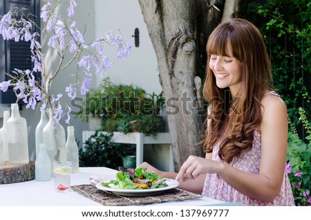 Pretty woman eating healthy green salad outdoors in garden, relaxed and happy in alfresco dining - stock photo