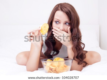 pretty woman eating potato chips in bed at home  and scared of gaining weight - stock photo