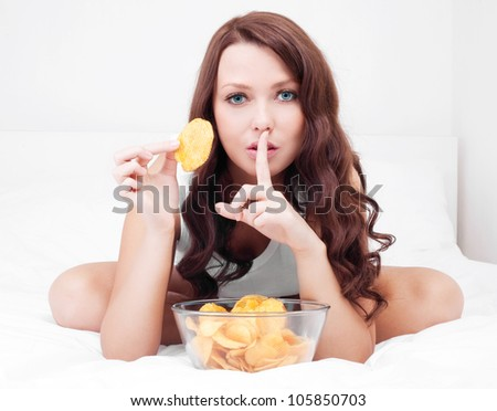pretty woman eating potato chips in bed at home with finger on her lips - stock photo