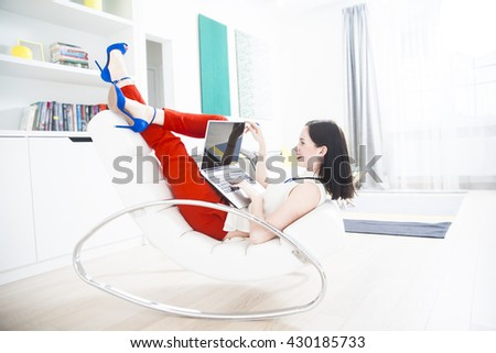 Pretty woman, elegant stylish lady working on her laptop while sitting in an white leather modern armchair. young adult girl wear red trousers and blue high heel. legs up - stock photo